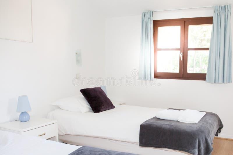 Poca sola cama en dormitorio con las ventanas en sol fotografía de archivo libre de regalías