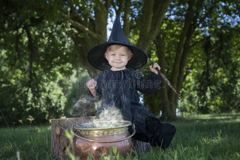 Poca strega di Halloween con couldron all'aperto fotografia stock libera da diritti