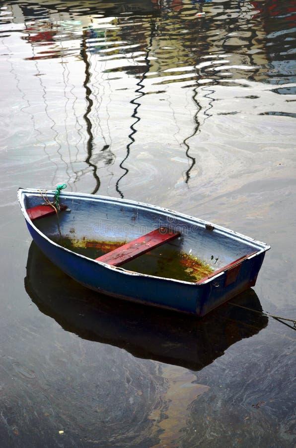Poca vecchia barca su acqua oleosa immagini stock