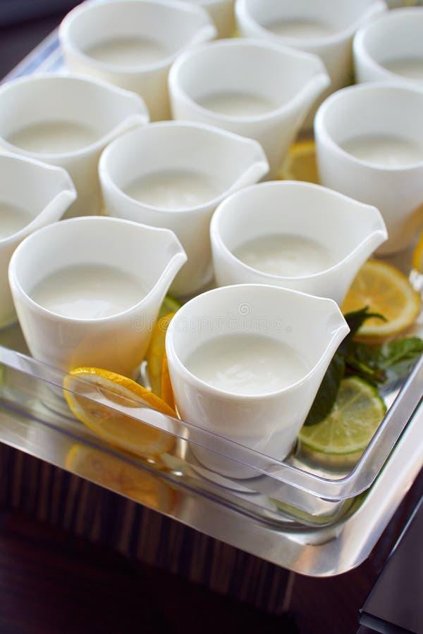 Pocas tazas de leche servidas para el desayuno imagen de archivo libre de regalías
