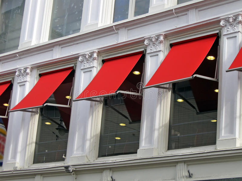 Pocas ventanas rojas del edificio, detalles de la construcción, fotografía de archivo