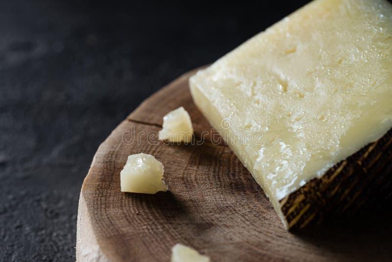 Pocenie ciężkiego sera Hiszpański manchego na drewnianym cięciu na ciemnym nieociosanym tle fotografia royalty free