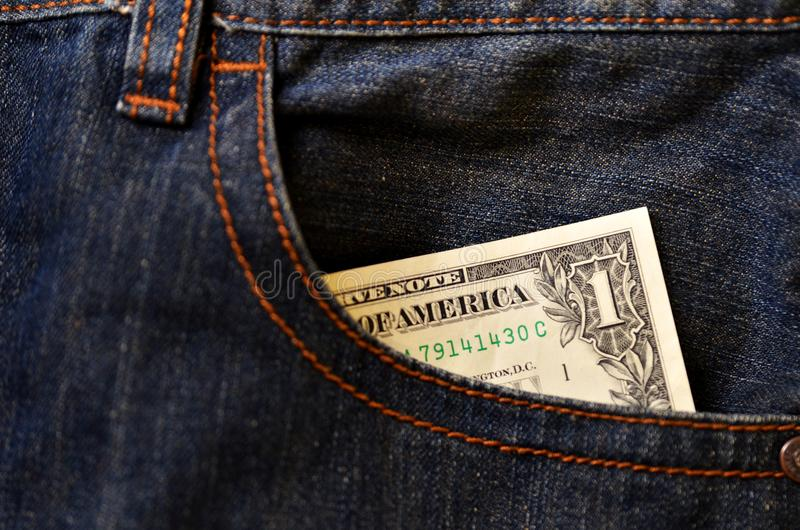 Poche de jeans avec des billets de banque de l'un dollar image stock