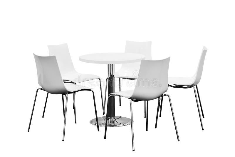 Poche sedie intorno alla tavola, nessuno, isolata su fondo bianco immagini stock