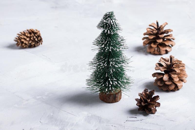 Pochi albero di Natale e coni su fondo concreto fotografia stock libera da diritti