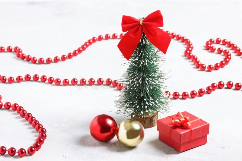 Pochi albero di Natale, regalo rosso e palle su fondo concreto fotografia stock libera da diritti