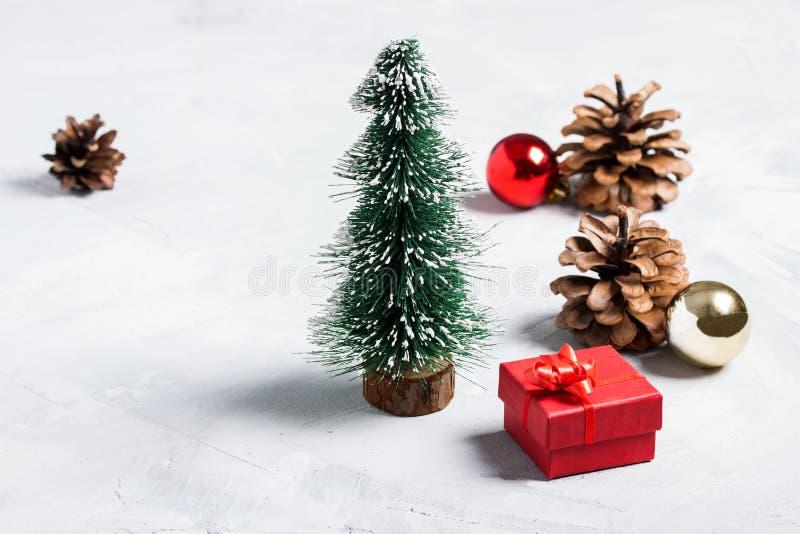 Pochi albero di Natale, regalo rosso, palle e coni sul BAC del calcestruzzo fotografie stock