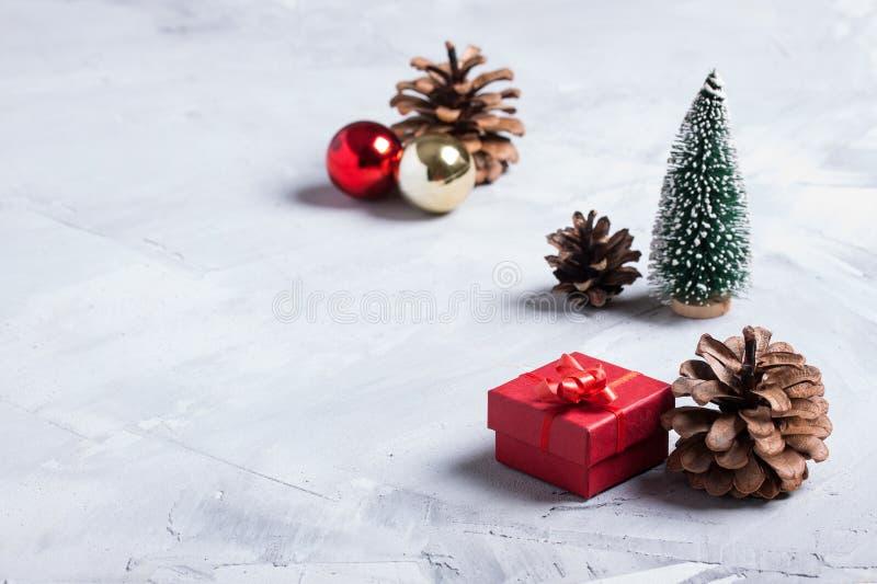 Pochi albero di Natale, regalo rosso, palle e coni sul BAC del calcestruzzo fotografia stock