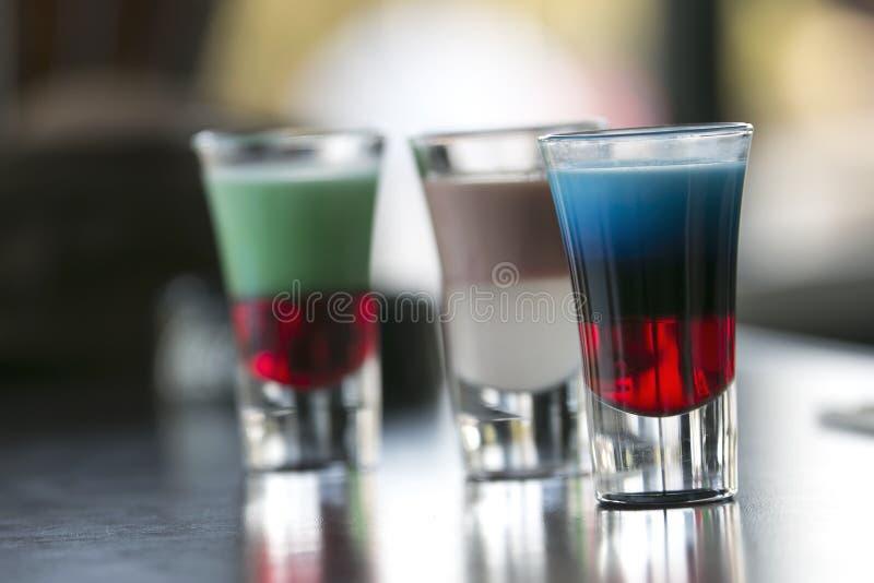 Pochi coctails dell'alcool alla barra vicino allo stagno fotografia stock