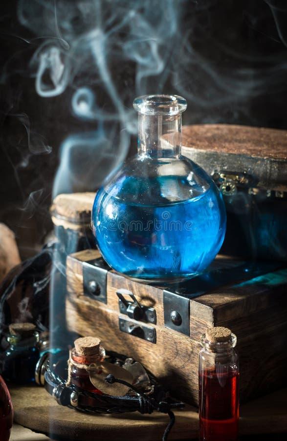 Poción mágica azul con humo imagen de archivo
