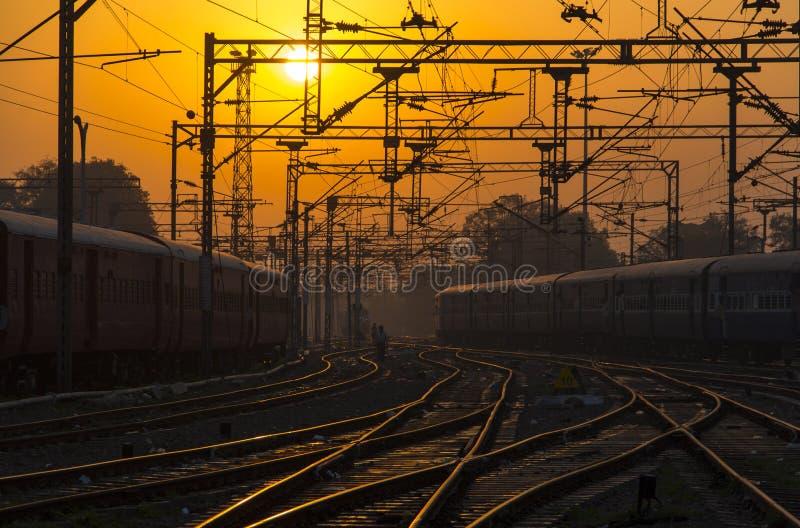 Pociąg, linia kolejowa, Kolejowi ślada przy Specjalizowałem się dworcem przy zmierzchem, wschód słońca zdjęcia royalty free