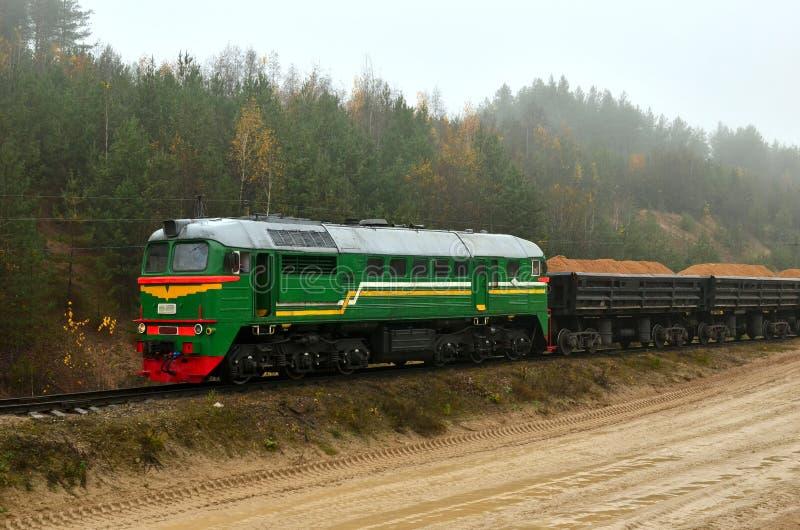 Pociąg towarowy odtransportowywa piasek z frachtowymi furgonami w piasek jamie w chmurnej mgłowej pogodzie obrazy stock