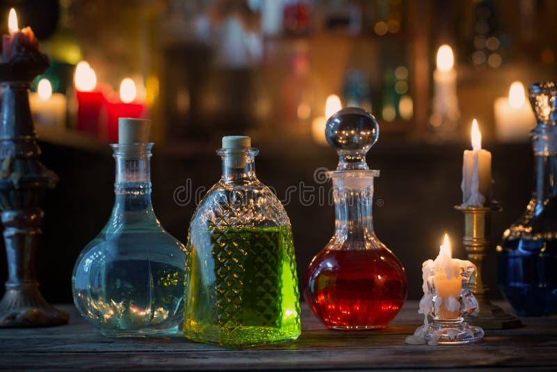 Pociones mágicas en botellas en fondo de madera imagenes de archivo