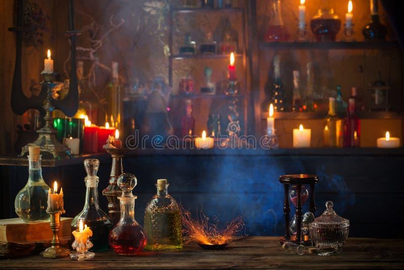 Pociones mágicas en botellas en fondo de madera imagen de archivo libre de regalías