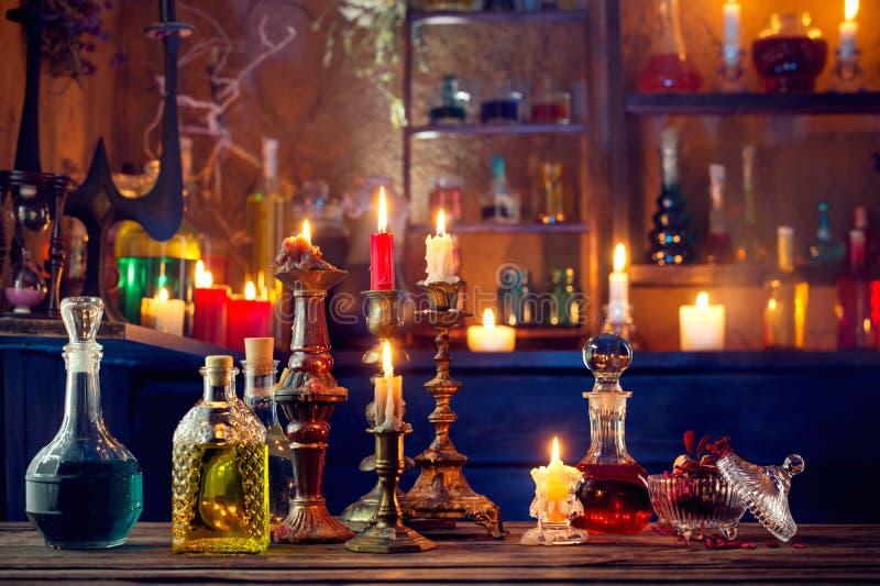 Pociones mágicas en botellas en fondo de madera foto de archivo