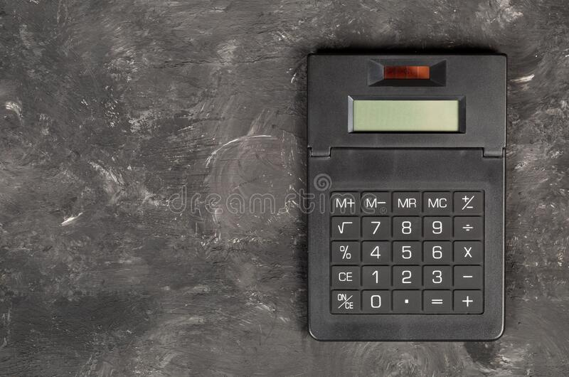 Pocket calculator on dark black background - tax, finance or accounting concept, top view flat lay from above royalty free stock photo