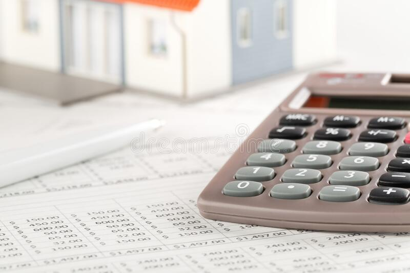 Pocket calculator with pen on financial analysis sheets with house model, real estate investment or poroperty costs concept royalty free stock images