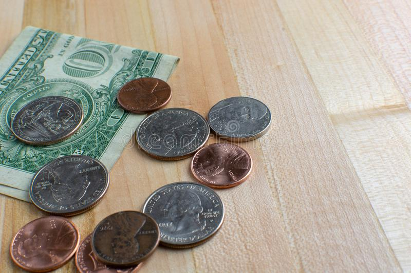 Pocket Change and Dollar Bill on Table. Pocket change and a folded dollar bill placed onto a wooden table. USA currency stock images