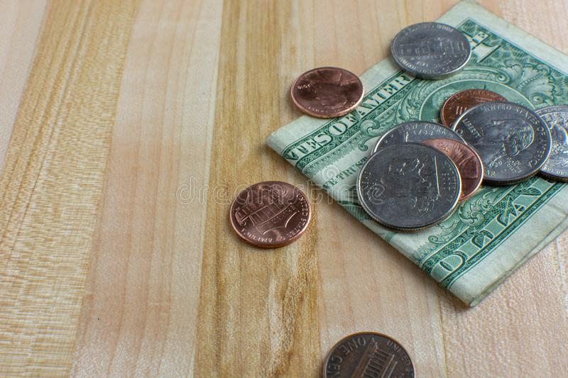 Pocket Change and Dollar Bill on Table. Pocket change and a folded dollar bill placed onto a wooden table. USA currency royalty free stock photo