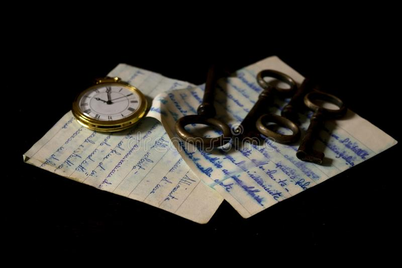 Pocket clock  and keys on an old handwritten sheet royalty free stock image