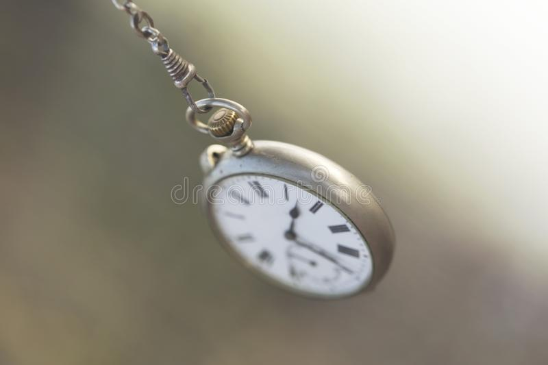 Pocket clock swings like the inexorable flow of time royalty free stock photo