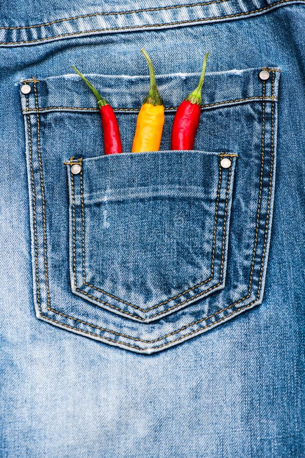 Pocket of jeans staffed with red and yellow chilly peppers, denim background. Peppers in back pocket of blue jeans. Piquant secret in pocket of pants, top view royalty free stock photography