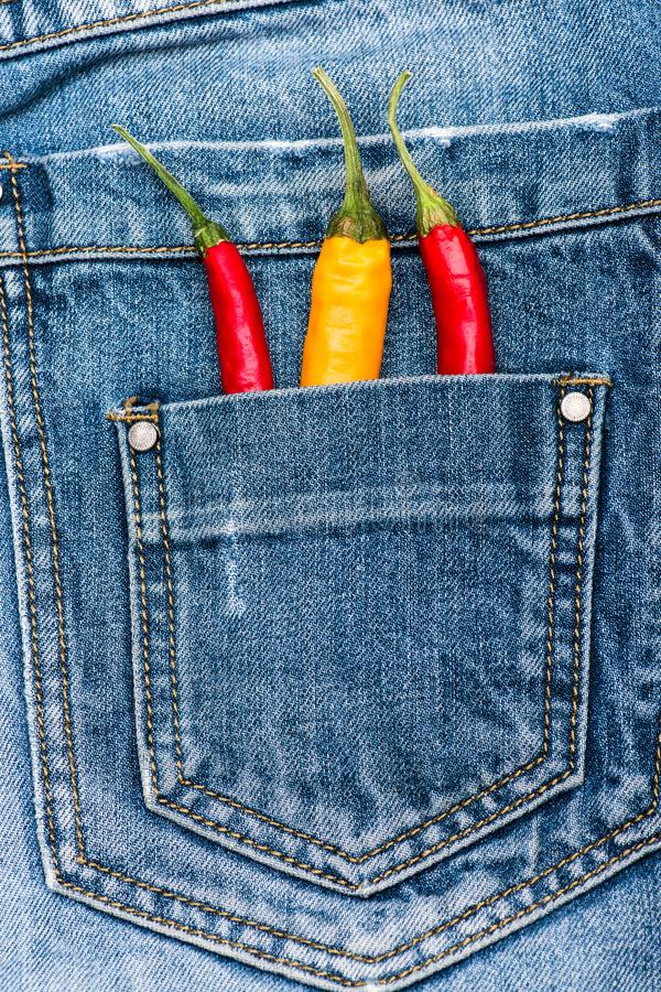 Pocket of jeans staffed with red and yellow chilly peppers, denim background. Peppers in back pocket of blue jeans. Hot. Sensations concept. Piquant secret in stock image