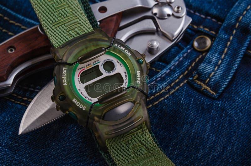 Pocket knife and electronic watches. Folding pocket knife and electronic watches over jeans royalty free stock image