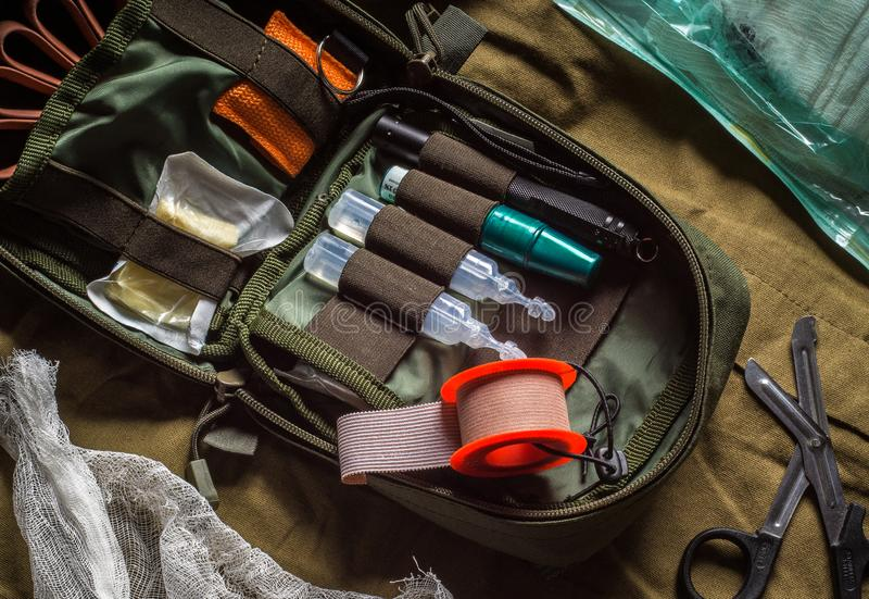 Open first aid kit with drugs and medical instruments on olive textile background. First aid in an emergency stock photography