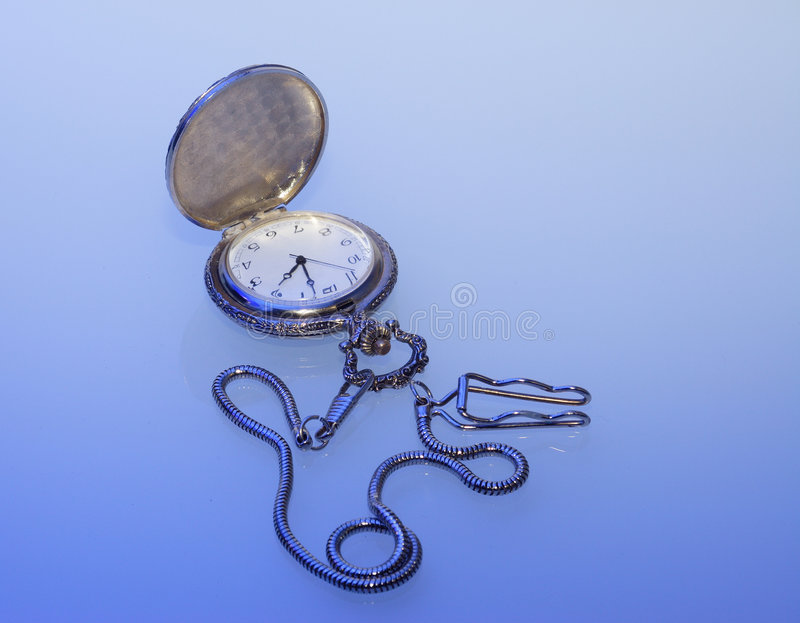 Pocket watch and blue light. Pocket watch with watch-chain on blue light stock images