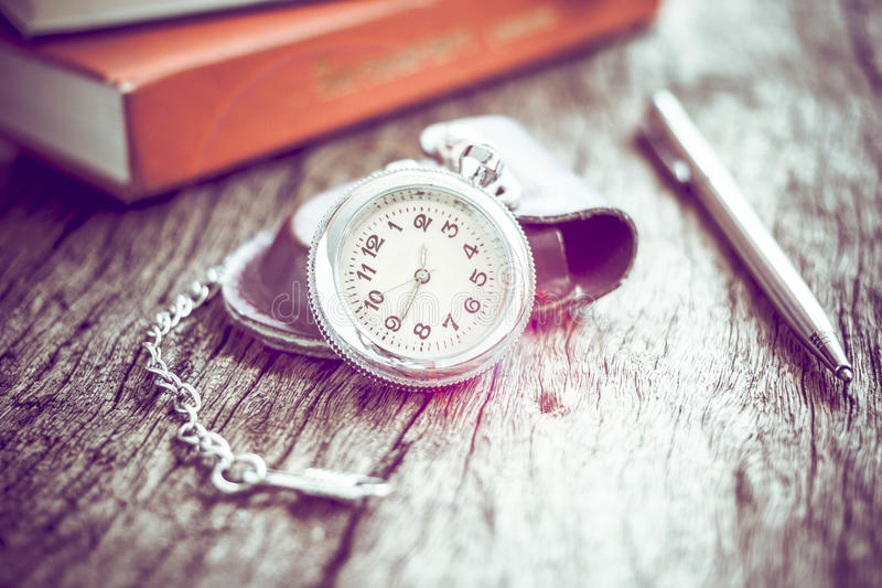 Pocket watch and book with pen, On old textured wood. stock photos