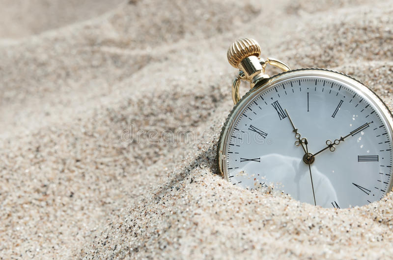 Pocket watch buried in sand stock photography