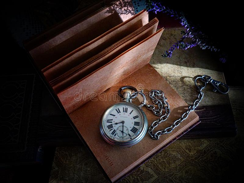 Pocket watch with chain on the notebook stock photo