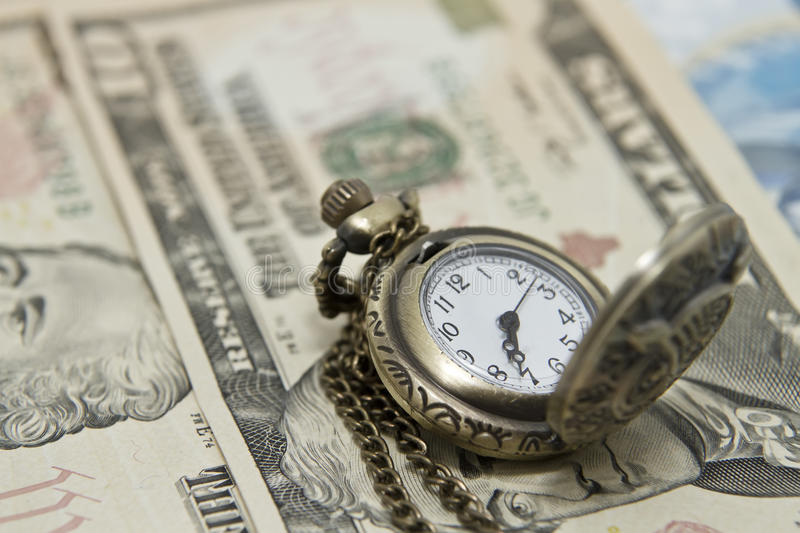 Pocket watch lie on dollars. Watch shows 7:36 (19:36 stock image