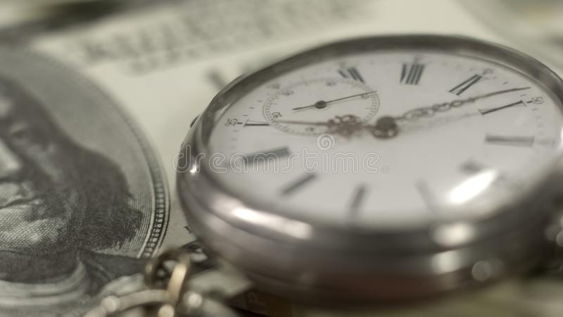 Pocket watch lying on one hundred dollar bill time is money, finance and banking royalty free stock photography