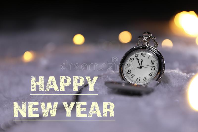 Pocket watch and message HAPPY NEW YEAR on snow. royalty free stock images
