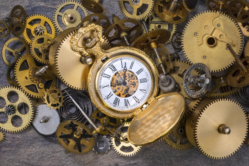 Pocket Watch and old Clock Parts - Cogs, gears, wheels. Pocket watch and a selection of dusty old brass clock parts royalty free stock photos