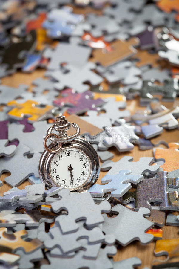 Pocket watch on a pile of jigsaw puzzle pieces. Shallow depth of field royalty free stock photography