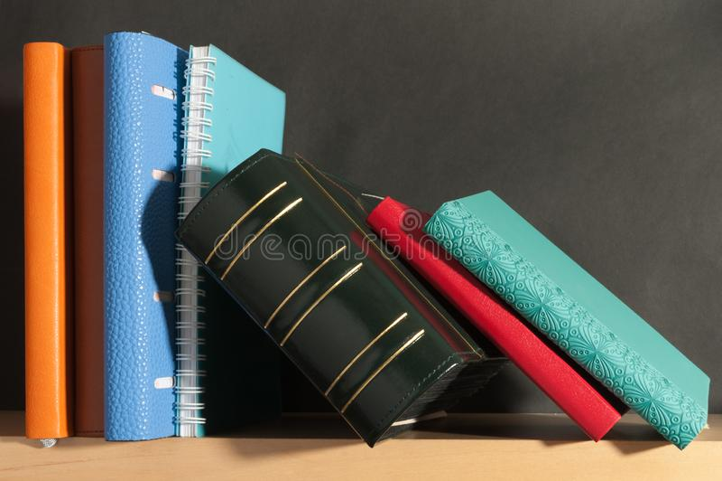 Pocketbook on the bookshelf. Notebook diary on black background on the bookshelf royalty free stock photos