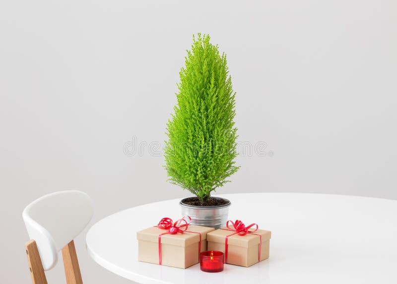 Poco árbol de navidad y regalos en una tabla imagenes de archivo