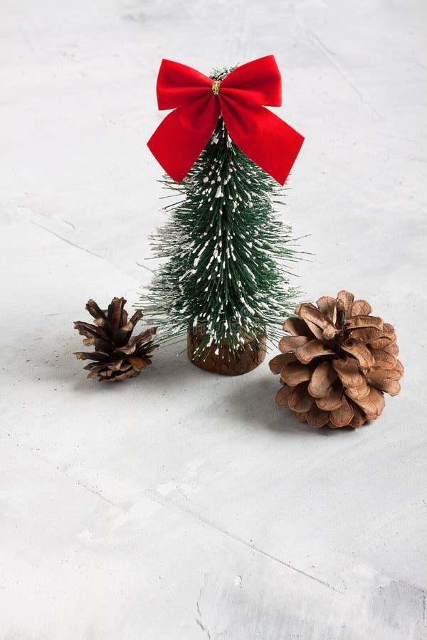 Poco albero di Natale e coni su fondo concreto immagini stock
