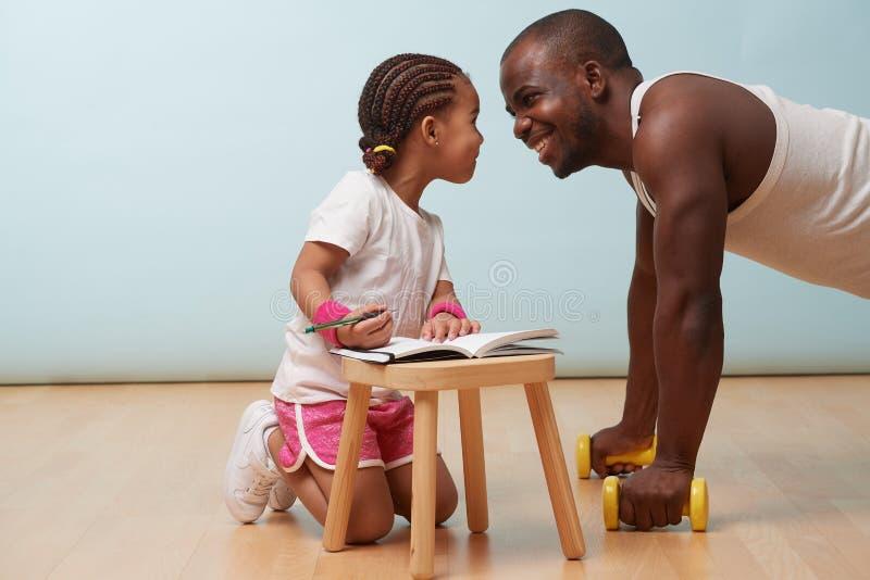 Poco aptitud de la hija que entrena a su padre Fabricación de notas Juego del papel del niño fotografía de archivo