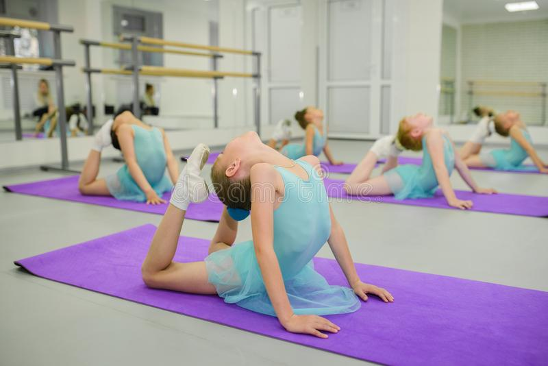 Poco bailarinas durante estirar ejercicios en clase de escuela del ballet fotografía de archivo libre de regalías
