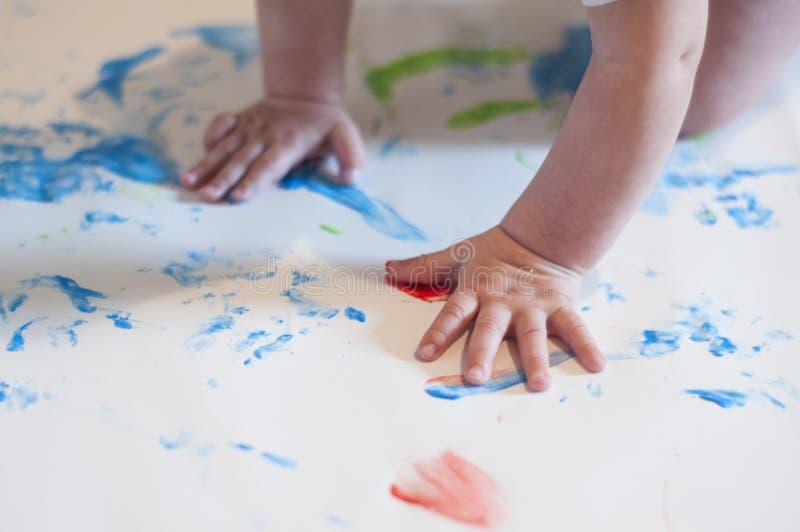 Poco bambino è impegnato nella pittura del dito Sviluppo iniziale Todler che gioca con le pitture su carta da disegno Le mani del immagine stock