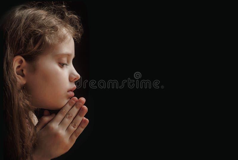 Poco bambino ha piegato la sua mano con pregare nel fondo nero fotografia stock libera da diritti