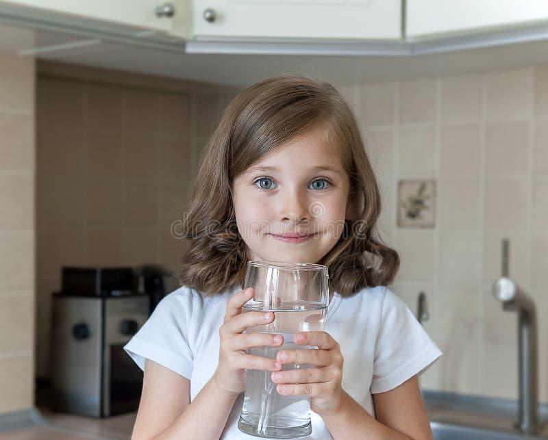 Poco bambino sta bevendo l'acqua pulita a casa, fine su La ragazza sveglia caucasica con capelli lunghi sta tenendo un tubo di li fotografia stock libera da diritti