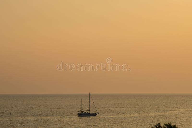 Poco barco de navegación en el océano con la puesta del sol suave anaranjada Corfú, Grecia del color del amazin fotografía de archivo libre de regalías