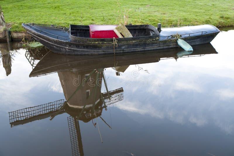 Poco barco y reflexión del molino de viento holandés en el agua foto de archivo