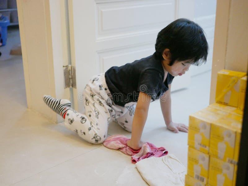 Poco bebé asiático que limpia su propio lío, polvo del cuerpo, en el piso de la casa imagenes de archivo