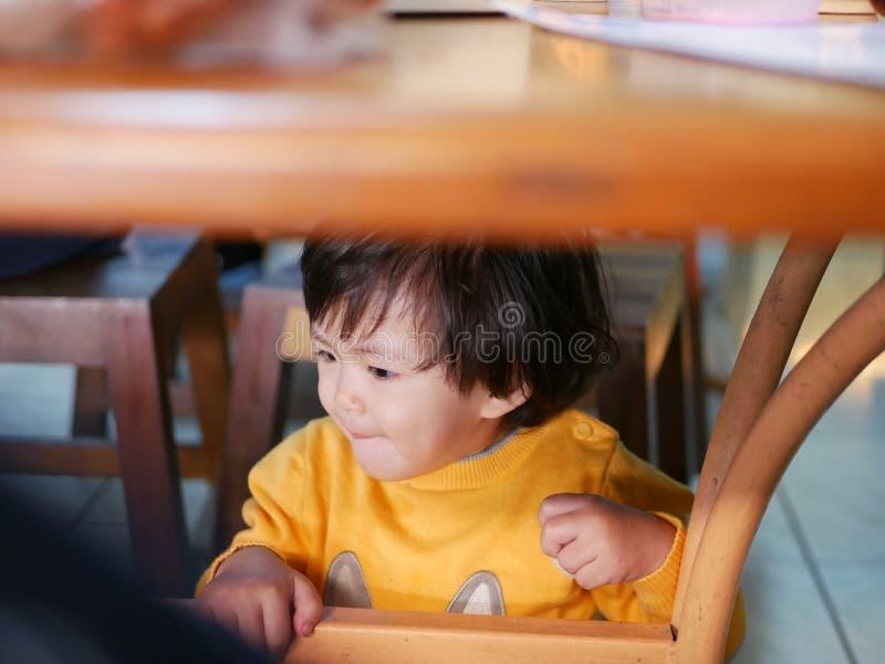 Poco bebé asiático que se sienta y que juega/que explora debajo de una tabla dinning durante una comida con su familia en un rest fotos de archivo
